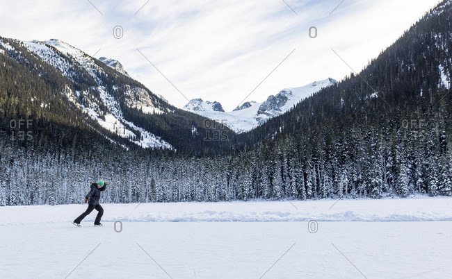 A Girl Ice Skates On A Cold Winter Day On Joffre Lake In British Columbia