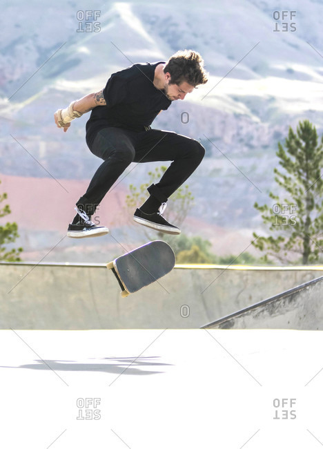 Man Performing Kickflip While Skateboarding On Flat Ground