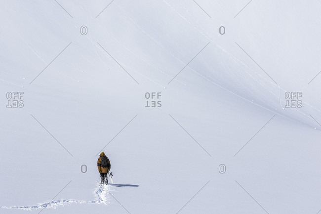 Snowboarder Hiking Across Glacier Of Fresh Snow And Leaves A Track Of Footprints Behind Him