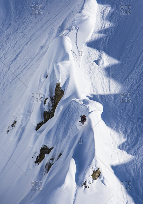 Snowboarder Riding Spine Line And Airs Of The End On A Sunny Bluebird Day