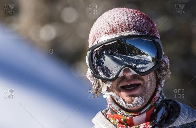 Male Snowboarder Looking At The Camera With Face Covered In Snow