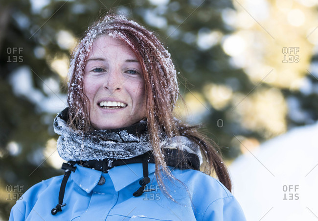 Portrait Of Smiling Female Snowboarder With Hair Covered In Snow