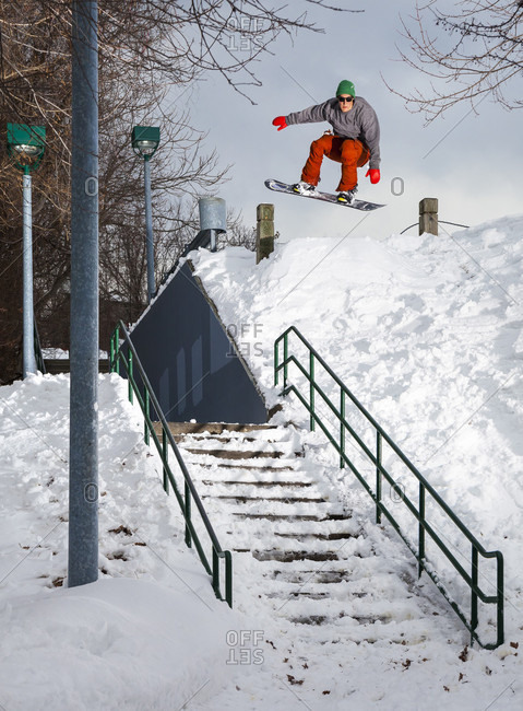 Male Snowboarder Jumping Over A Staircase In New England