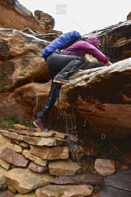 Woman Bouldering On Rock Navigating Waterfall