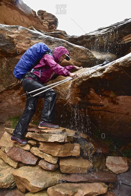 Woman Climbing Rock Navigating Waterfall In Canyonlands National Park