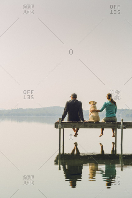 Man And Woman With Their Dog Sitting On Dock On Caspian Lake