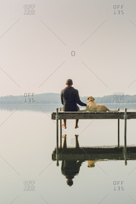Man And Dog Sitting On The Edge Of A Dock On Caspian Lake