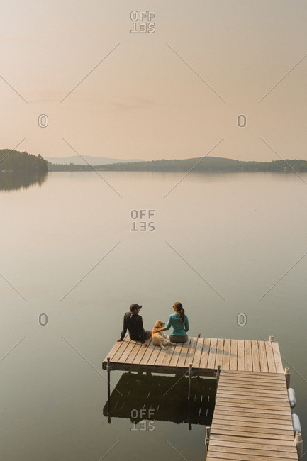 View Of Man And Woman With Dog Sitting On Edge Of Dock On Caspian Lake