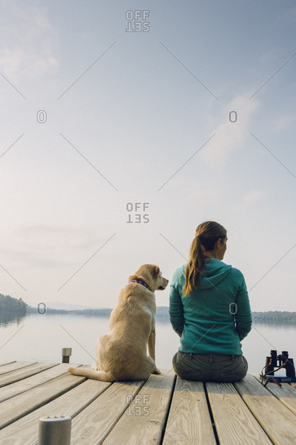 Rear View Of Woman And Dog Sitting On Edge Of Dock In Caspian Lake