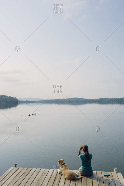Woman With Her Dog Sitting On Dock Looking At Birds With Binoculars In Caspian Lake