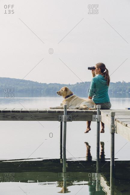 Woman With Her Dog Sitting On Dock Using Binoculars In Caspian Lake