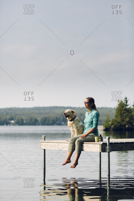 Woman And Dog Sitting On The Edge Of Dock On Caspian Lake