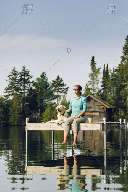 Woman With Her Dog Sitting On The Edge Of Dock On Caspian Lake