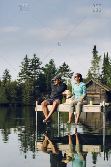 Man And Woman With Their Dog Relaxing On Edge Of Dock On Caspian Lake