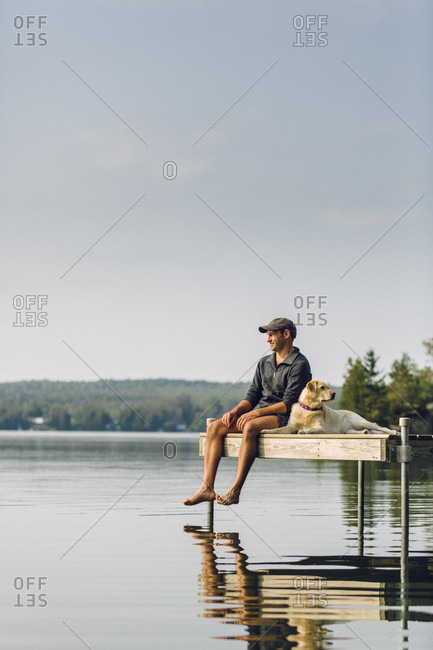 Man Enjoying View With His Dog On The Edge Of A Dock On Caspian Lake