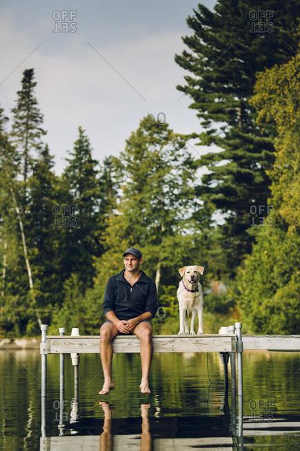 Smiling Man And Dog Sitting On Edge Of Dock On Caspian Lake