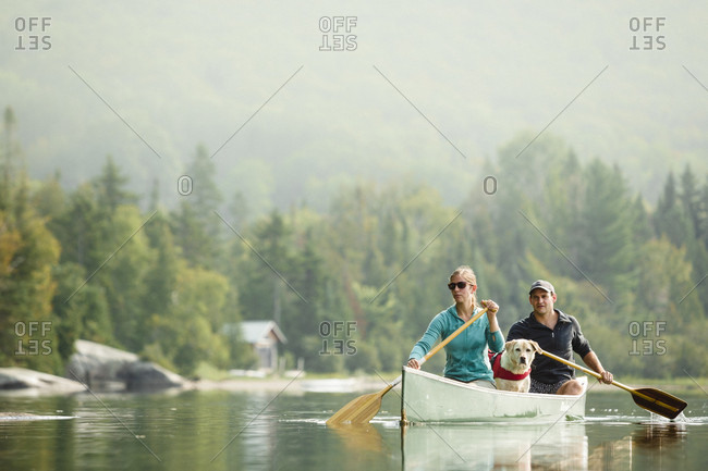 Man And Woman Canoeing With Their Dog On Caspian Lake