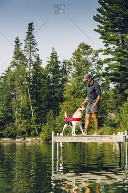 Man With His Dog On The Edge Of A Dock On Caspian Lake