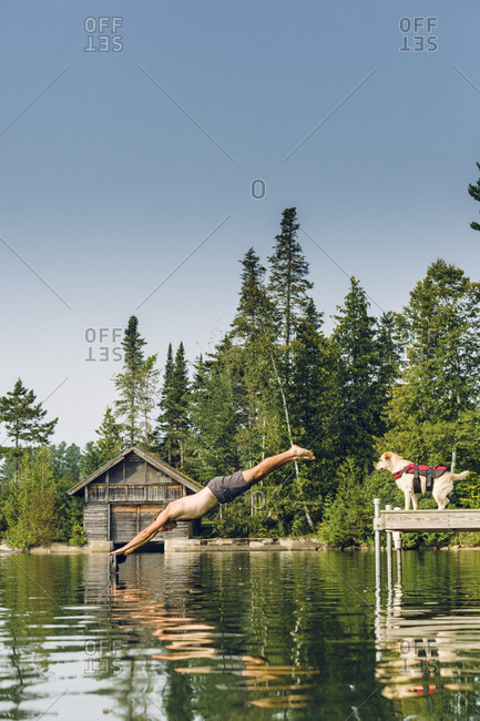 Man Diving Into The Water While His Dog Looks On From The Edge Of Dock
