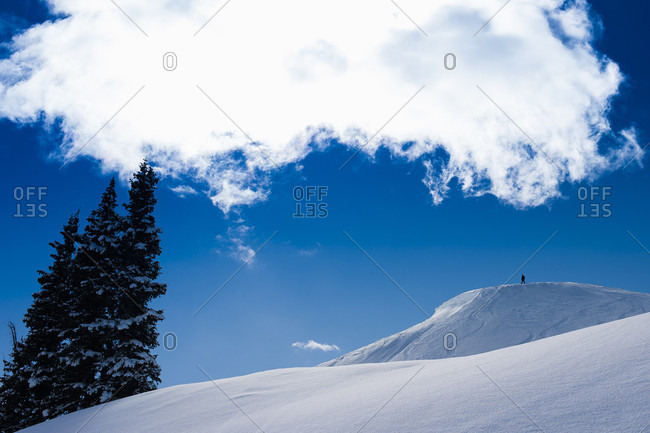 Long Exposure Of Snowboarder Standing On Top Of Mountain