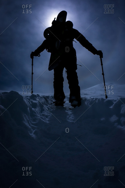 Silhouette Of Snowboarder Hiking On Mountain