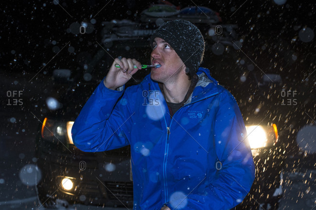 Man Brushing Teeth In A Snow Storm During Night