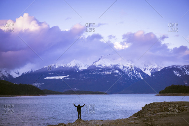 Person Standing At Edge Of Lake During Sunset