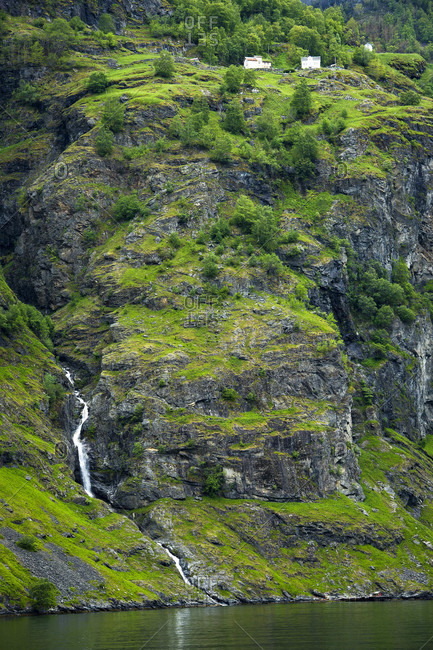 A House On A Cliff Above A Waterfall Along The Sognefjord In Norway