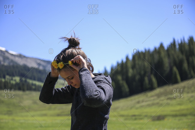 Girl Putting Flower Crown In Her Hair While Walking In A High Mountain Meadow