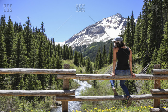 Girl Sitting On Rail Fence Exploring Colorado Creek In The San Juan Mountains