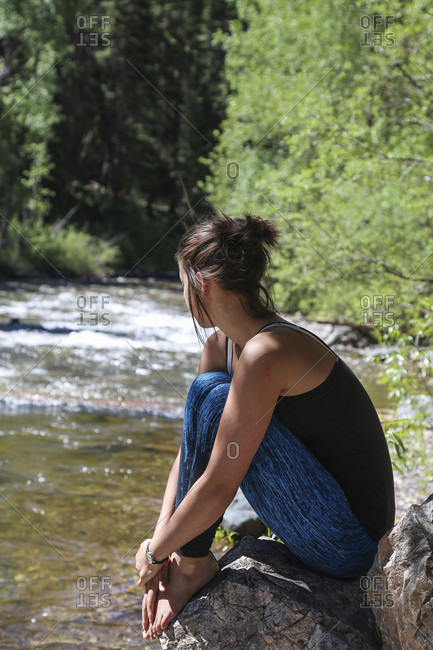 Woman Sitting On Rock Thoughtfully Beside A Colorado Creek