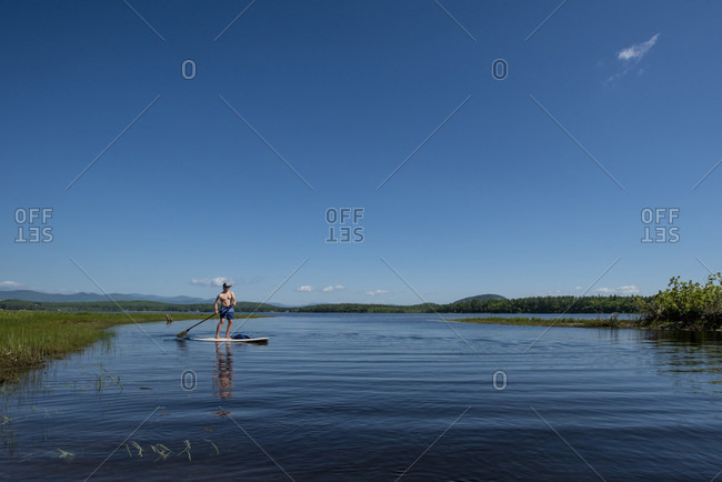 Man Paddleboarding On A Calm Lovewell Pond In Maine