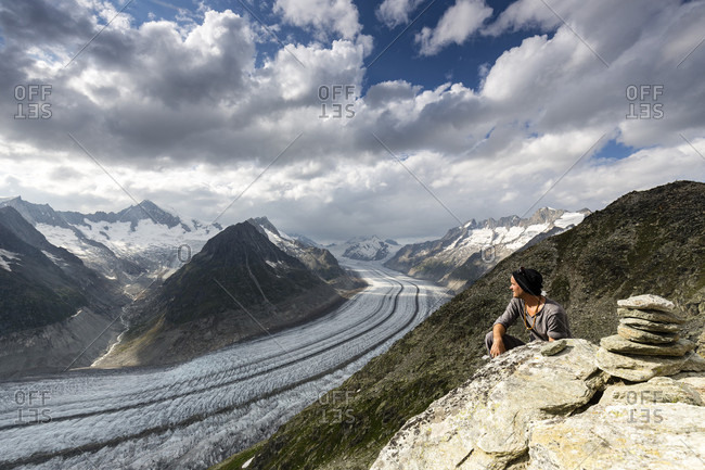 Man Peeking Out Over The Aletsch Glacier In The Canton Of Wallis, Switzerland