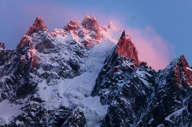 Alpine Peaks With A Snowy Glacier Pouring Down The Rocky Mountain In Chamonix, France