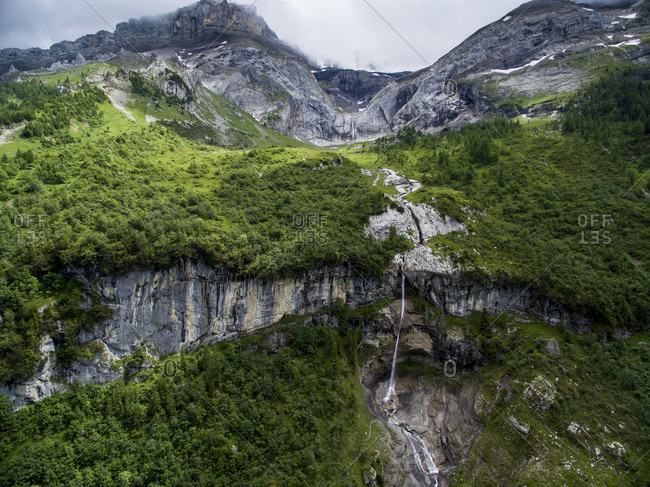 Alpine Landscape With A Waterfall Tumbling Over A Rocky Ledge In Canton Bern, Switzerland