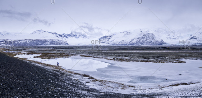 Long Exposure Of Hiker Making His Way Across The Icelandic Wintery Landscape In Iceland