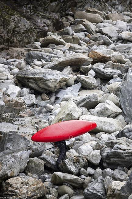 Kayaker Carrying His Kayak On Rocky River Bank Along The Reuss River