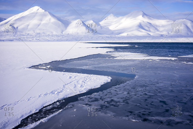 Mountain Landscape On A Clear Sunny Day In The Arctic Sea With A Break In The Pack Ice