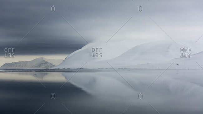 Reflection Of Snowy Mountains In The Arctic Sea In Spitzbergen