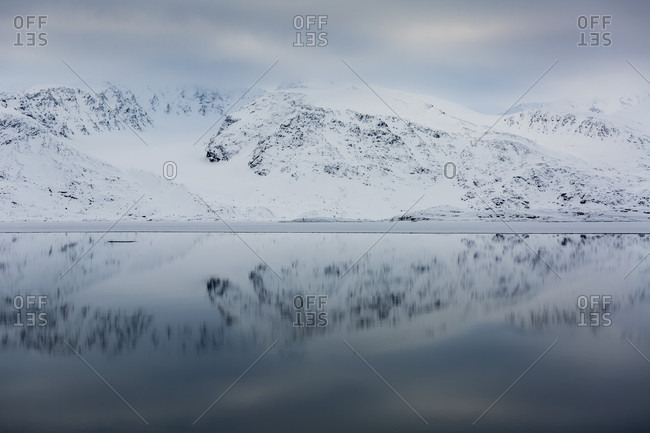 Reflection Of Rocky And Snowy Arctic Mountains In The Arctic Sea