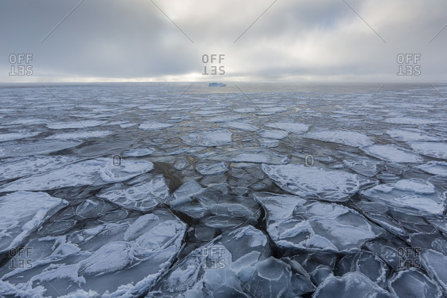 Fragmented Ice Pack With Iceberg In The Background And Cloudy Winter Sky In Spitzbergen, Svalbard