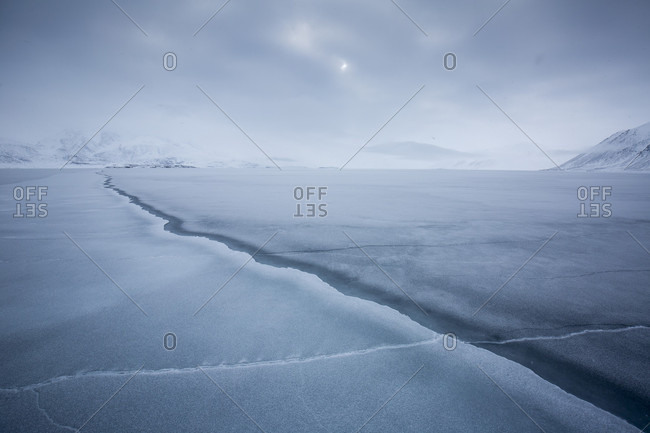 A Cut In The Pack Ice Leading To Snowy Mountains In The Background In Spitsbergen, Svalbard