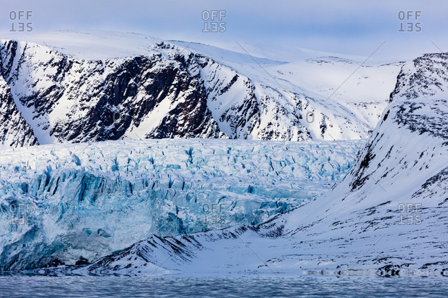 Rocky And Snowy Mountains Surrounding The Glacier And The Arctic Sea In The Foreground