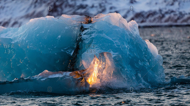 Piece Of Glacier On The Arctic Sea With The Sun Reflecting On It During Sunset In Spitsbergen, Svalbard