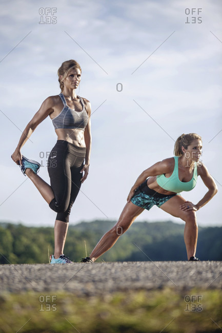 Two Women Doing Stretching Exercise On Street