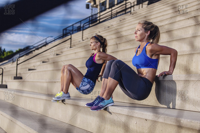 Two Women Doing Exercise On Staircase