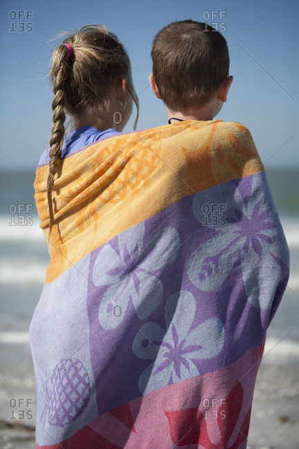 Two Young Children Wrapped In A Beach Towel Looking At Ocean