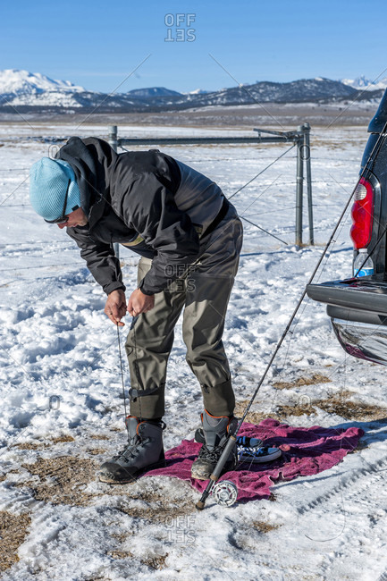 Man Lacing Up Wader Boots On The Upper Owens River