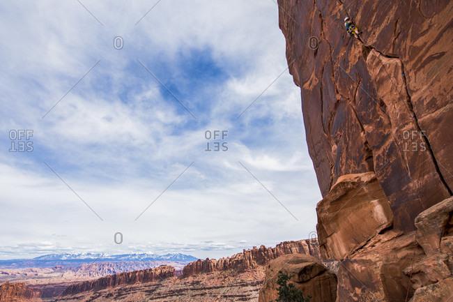 Woman Rock Climbing Outside Of Moab, Utah