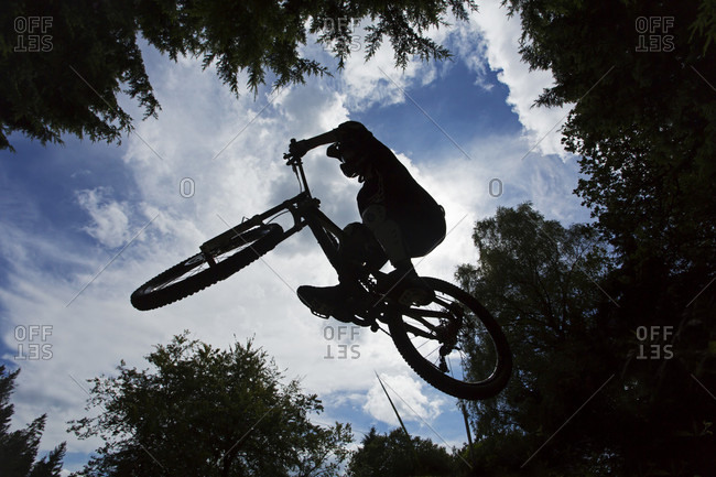 Silhouette Of Man Jumping On Mountain Bike In Gloucestershire, Uk